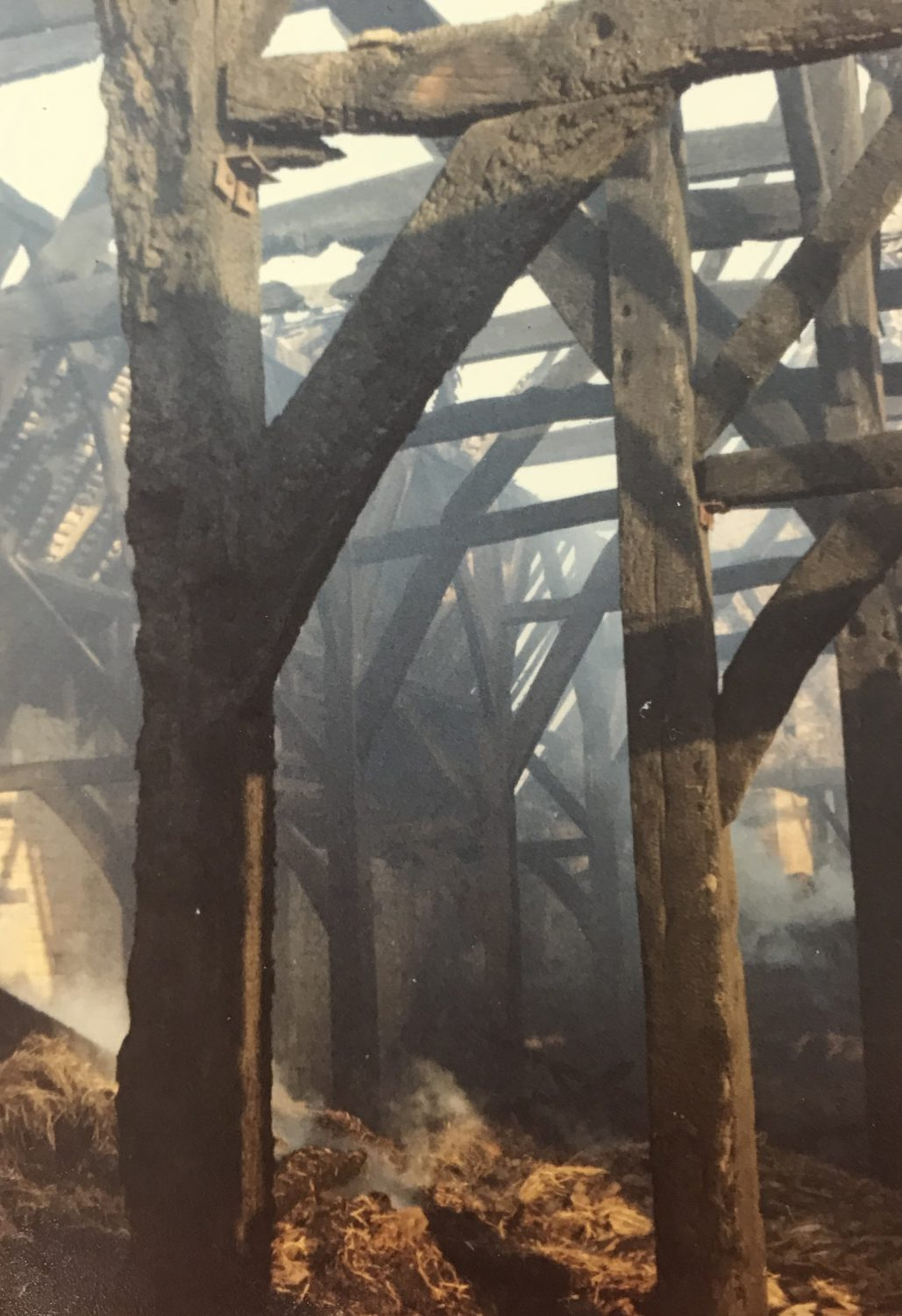 Smouldering hay and blackened timbers in the aftermath of the fire