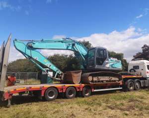 A digger being delivered to site